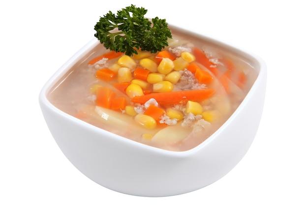 Kuchnia azjatycka, chińska zupa kukurydziana z ziemniakami, marchewką i kurczakiem w misce, ozdobiona gałązką pietruszki, na białym tle.