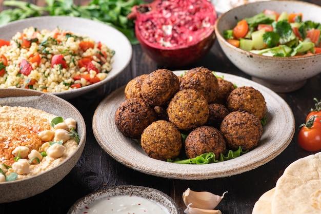 Kuchnia bliskowschodnia lub arabska, falafel, hummus, tabouleh, pita i warzywa na drewnianym stole, selektywne skupienie