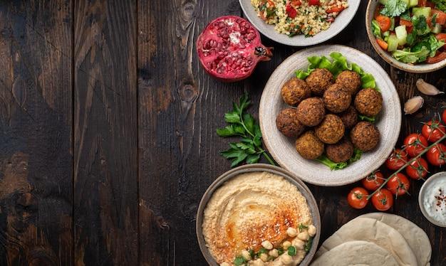 Kuchnia bliskowschodnia lub arabska, falafel, hummus, tabouleh, pita i warzywa na drewnianym tle, widok z góry, miejsce na kopię