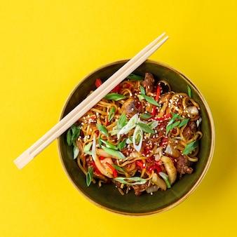 Kuchnia chińska, makaron z mięsem smażony kurczak smażony z warzywami w sosie sojowym i sezamem na woku. tradycyjne chińskie jedzenie.