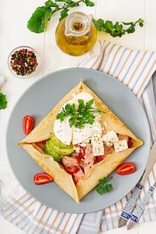 Kuchnia francuska. śniadanie, obiad, przekąski. naleśniki z jajkiem w koszulce, serem feta, smażoną szynką, awokado i pomidorami na białym stole. widok z góry