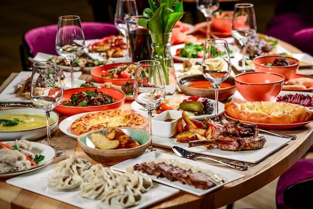 Kuchnia gruzińska. duży zastawiony stół z różnymi potrawami dla całej rodziny w dzień wolny.