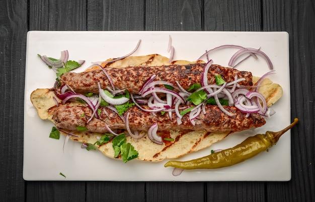 Kuchnia gruzińska - lulia kebab z grillowaną cebulą, tradycyjna kuchnia gruzińska, na pieczywie