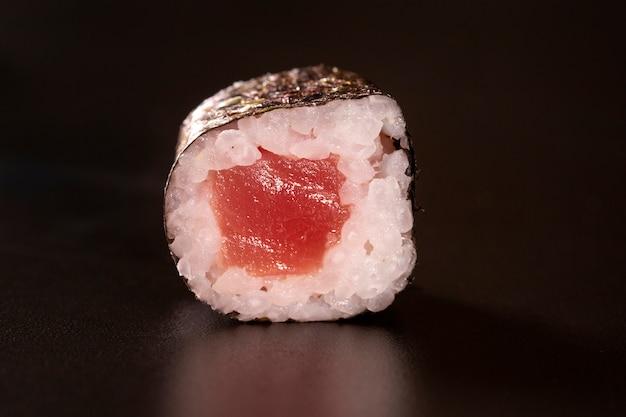 Kuchnia japońska. jeden pokój sushi roll odizolowane na czarnym tle closeup strza? u