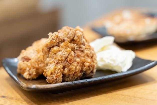 Kuchnia japońska, smażony kurczak zwany karaage, zawarty w czarnym naczyniu ustawionym na drewnianym stole