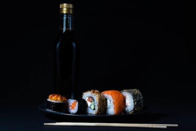 Kuchnia japońska sushi maki i nigiri na czarnym tle sos sojowy i drewniane patyczki stick