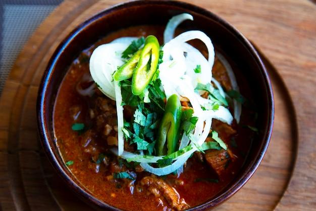 Kuchnia kaukaska. wołowina, koncentrat pomidorowy, cebula, papryka w naczyniu ceramicznym na drewnianym stojaku. restauracja serwująca dania kuchni gruzińskiej