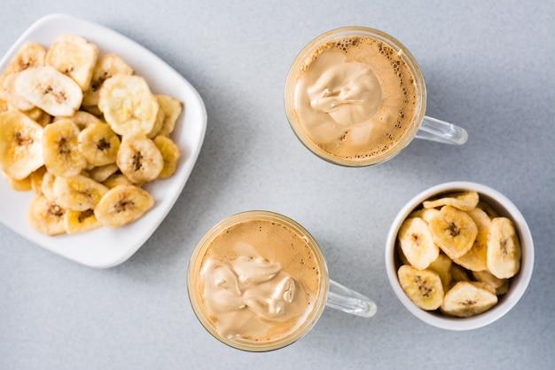 Kuchnia kwarantannowa. dwie filiżanki z kawą dalgona i chipsami bananowymi na szarym tle. widok z góry