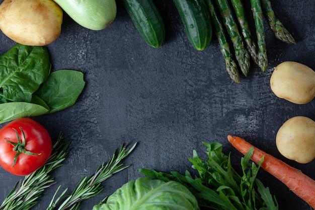 Kuchnia - świeże kolorowe organiczne, ekologiczne młode wiosenne warzywa na ciemnym tle kamienia. leżały płasko marchewki, pomidory, natka pietruszki, szparagi i rozmaryn. widok z góry wegańskie jedzenie. składniki z miejsca na kopię