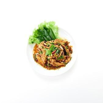 Kuchnia tajska pikantna sałatka z karkówki z grilla podawana ze świeżymi warzywami na białym tle