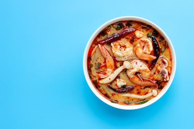 """Kuchnia tajska """"tom yam kung"""" w białej misce. gorąca i pikantna zupa na niebieskim tle."""