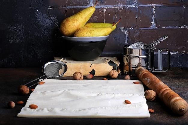 Kuchnia tło pieczenia w stylu retro cegła grunge ściana gruszka migdałowa ciasto filo wałek do ciasta sito