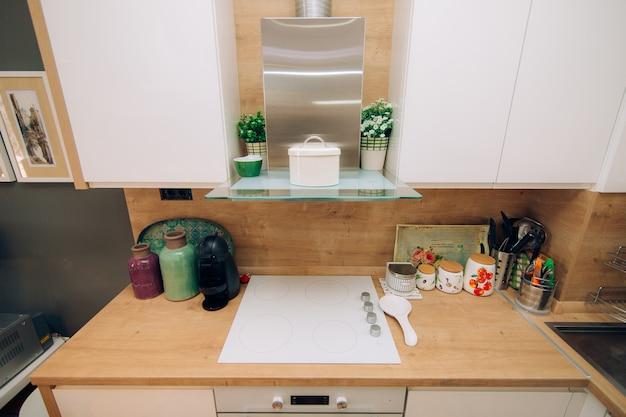 Kuchnia w mieszkaniu. projekt pokoju kuchennego. drewniana kuchnia, lodówka, kuchenka, stół jadalny. wnętrze kuchni