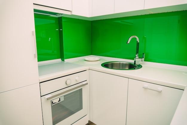 Kuchnia w mieszkaniu. projekt pokoju kuchennego. kuchnia drewniana, lodówka, kuchenka, stół jadalny. wnętrze kuchni.