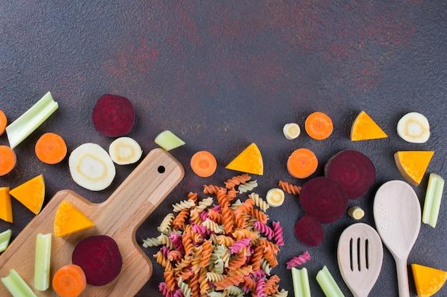 Kuchnia w tle. gotowanie pysznych zdrowych potraw. kolorowy suchy makaron z warzyw i jego naturalnych barwników warzywnych: seler, burak, marchew, dynia, pasternak.