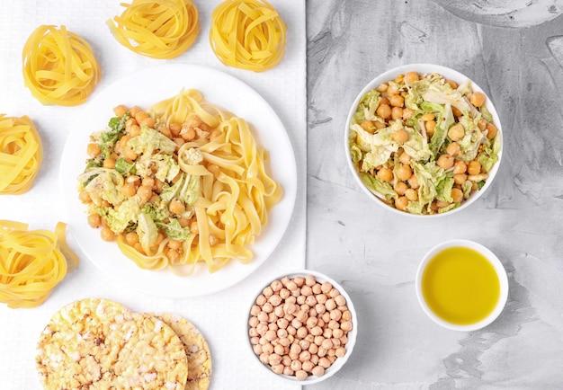 Kuchnia wegetariańska. sałatka z ciecierzycy i kapusty, makaronu, oliwy z oliwek, pieczywa chrupkiego. betonowe tło