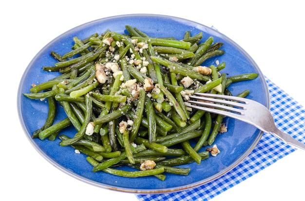 Kuchnia wegetariańska. smażona fasolka szparagowa z orzechami włoskimi. studio photo