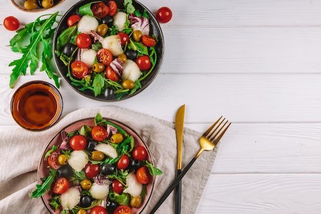 Kuchnia włoska dwie porcje sałatki z melonem, pomidorami i oliwkami