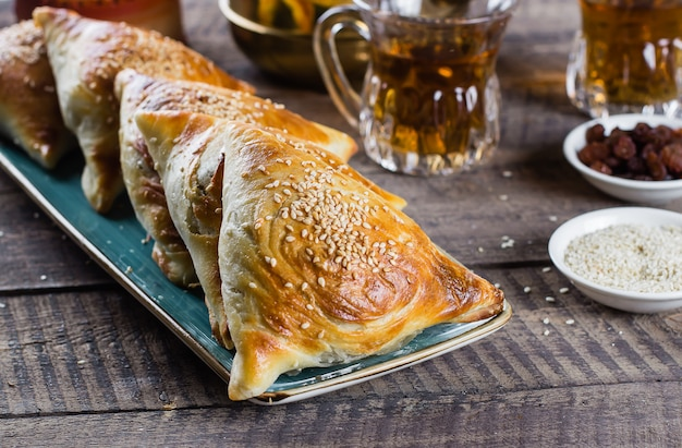 Kuchnia wschodnia. pyszne samosas samsa z mięsem, szklankę herbaty na drewnianym stole. jedzenie ramadan