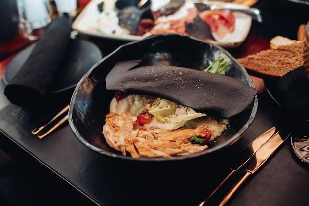 Kuchnia współczesna z serwowaną sałatką cezar z kurczakiem w czarnej misce pokrytej czarnym plastrem z sezamem.