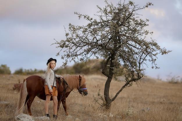 Kucyk lub mały koń jedzie na młodej kobiecie