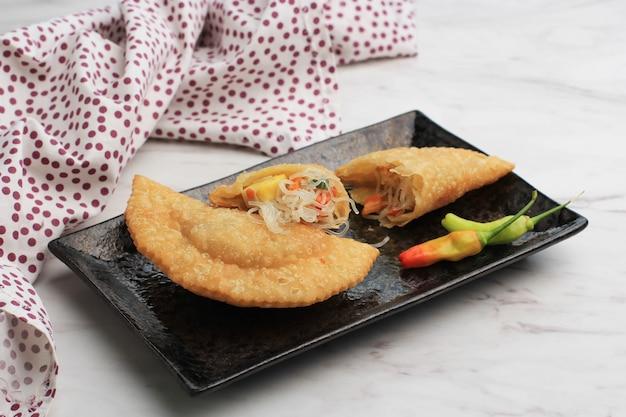 Kue pastel goreng (jalangkote lub karipap) to przekąska z kruche ciasto wypełniona pokrojoną w kostkę marchewką, ziemniakami i jajkami. popularny w azji południowo-wschodniej jako curry puff