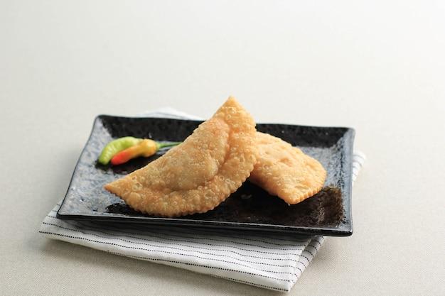 Kue pastel goreng lub karipap (curry puff) pusing, fried snack popularne w malezji i indonezji. z mąki nadziewanej curry marchewką i ziemniakami