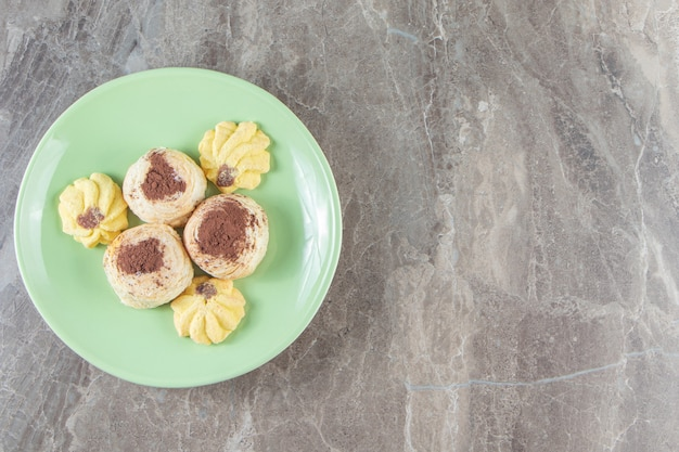 Kue semprits i proszek kakaowy na kruche ciasto na talerzu na marmurze.