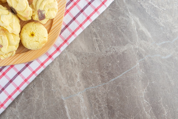 Kue semprits na drewnianym talerzu na ściereczce na marmurze.