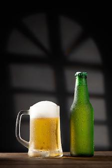 Kufel do piwa i butelka na ciemnym tle na drewnianej podstawie. z copyspace. format pionowy.