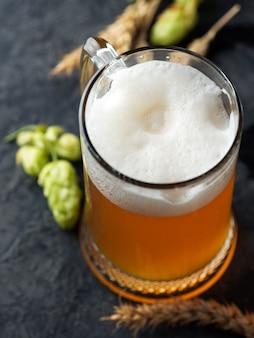 Kufel piwa na stole z pszenicy i zielonego chmielu