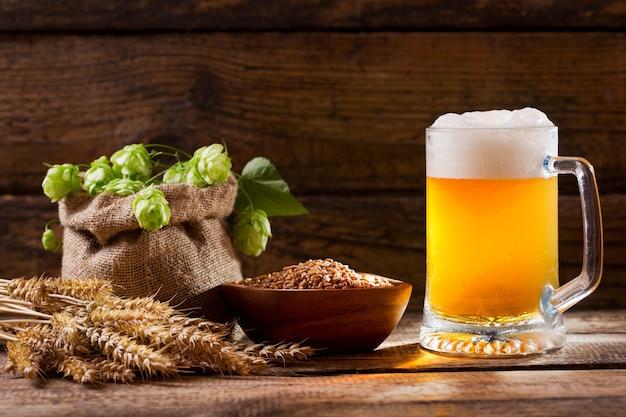 Kufel piwa z zielonym chmielem, kłosami pszenicy i ziarnami oraz na drewnianym stole