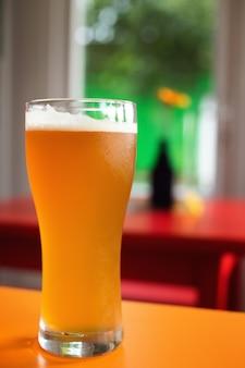 Kufel złotego piwa rzemieślniczego w kolorowym barze