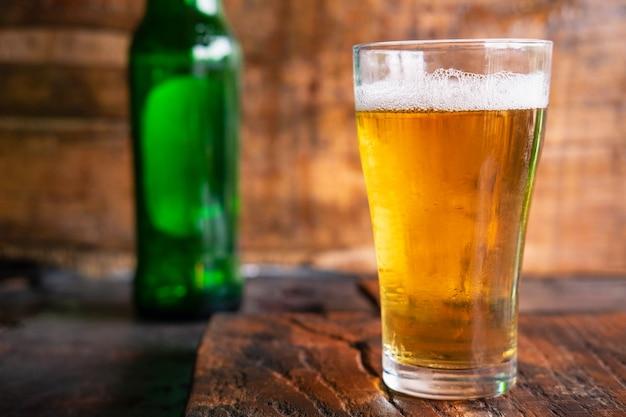 Kufle do piwa i butelki piwa na drewnianym stole