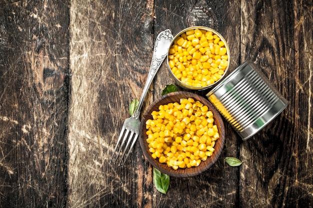 Kukurydza w puszce z widelcem na drewnianym stole.