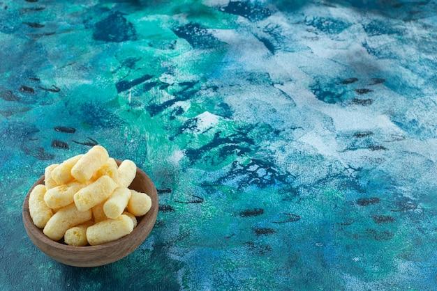 Kukurydziane paluszki w misce, na marmurowym stole.