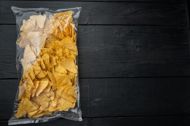 Kukurydziane tradycyjne trójkątne nachos w przezroczystym opakowaniu, na czarnym drewnianym stole, widok z góry lub płasko ułożony