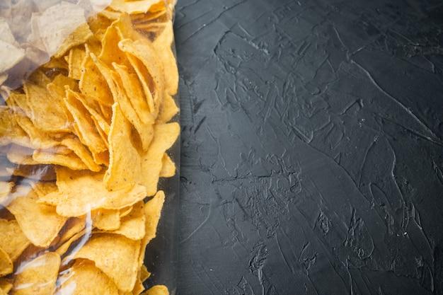 Kukurydziane tradycyjne trójkątne nachos w przezroczystym opakowaniu, na czarnym stole, widok z góry lub płasko ułożony