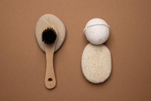 Kula do kąpieli o zapachu wanilii i szczotka w kompozycji spa z kamieniem na brązowo.