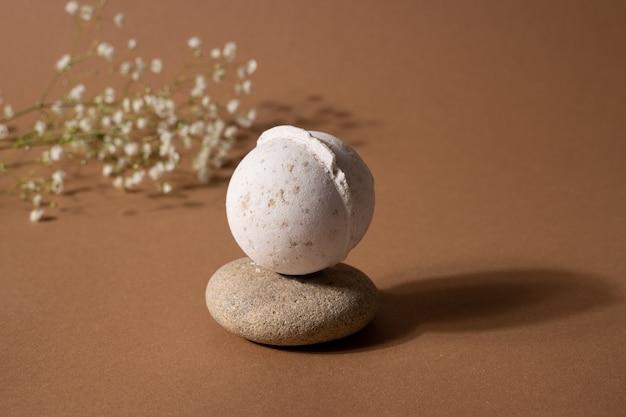 Kula do kąpieli o zapachu wanilii w kompozycji spa z suchymi kwiatami i kamieniem na brązowym tle.