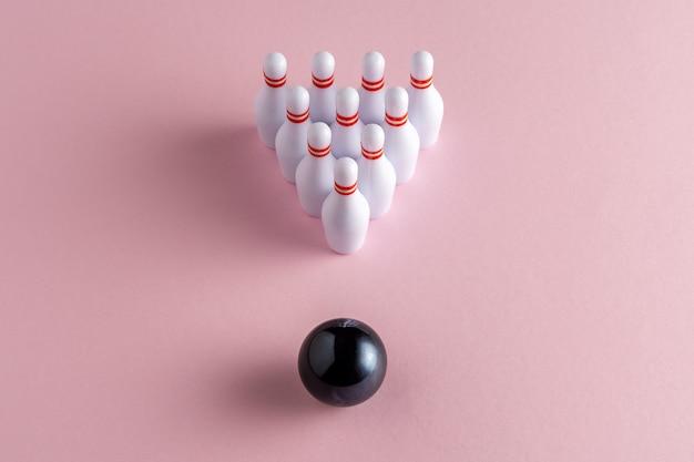 Kula do kręgli i białe kręgle na pastelowym różowym tle.