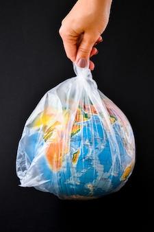 Kula w kształcie kuli ziemskiej jest w plastikowej torbie jako koncepcja plastikowego zanieczyszczenia ziemi