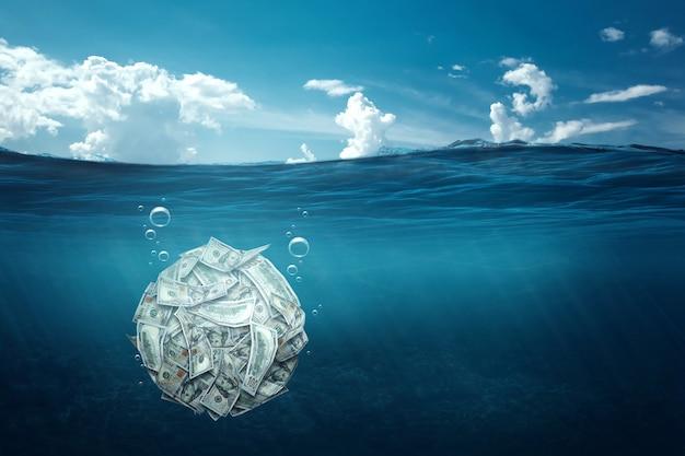 Kula z dolarów tonie pod wodą. koncepcja kryzysu finansowego, długi, płacenie rachunków, hipoteka, upadłość.