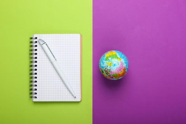 Kula ziemska i notebook na fioletowym zielonym tle. widok z góry. minimalizm. koncepcja edukacji, geografia