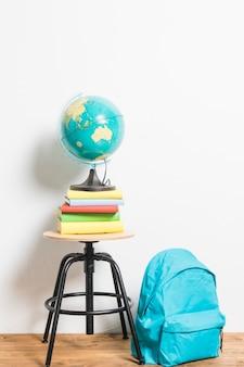 Kula ziemska na książkach umieszczonych na krześle taboretowym obok tornistra