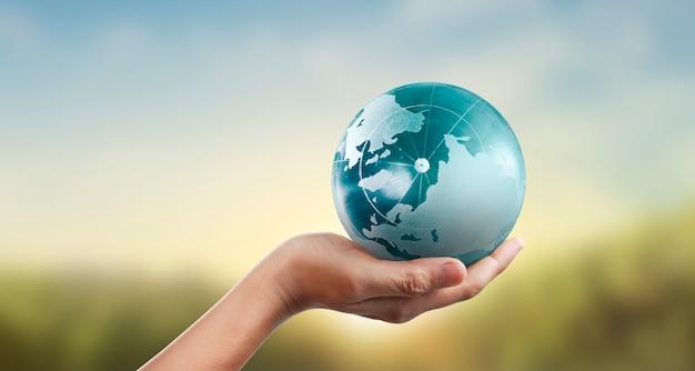Kula ziemska, ziemia w ludzkiej dłoni, trzyma świecącą naszą planetę