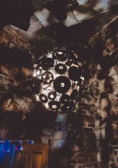 Kula żyrandolowa z metalowych kół zębatych ze światłem w środku, rzucająca cienie na kamienną ścianę, widok z dołu