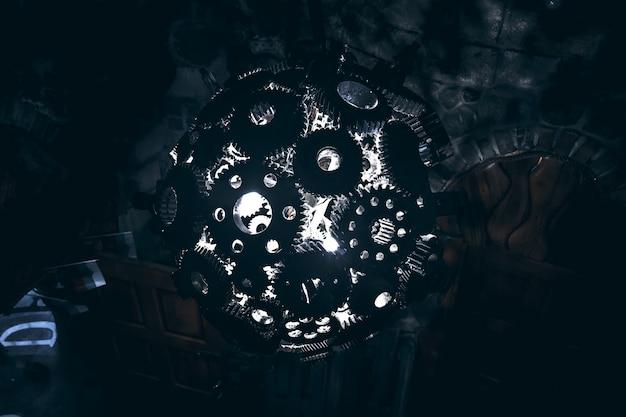 Kula żyrandolowa z metalowych kół zębatych ze światłem w środku, rzucająca cienie, widok z boku