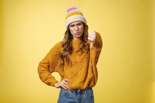 Kulawa niechęć przestań obserwować. portret rozczarowany, niezadowolony, wybredna młoda osądzająca kobieta pokazuje kciuk w dół, krzywiąc się, krzywiąc się, niezadowolony, wyrażając dezaprobatę, antypatię, żółte tło