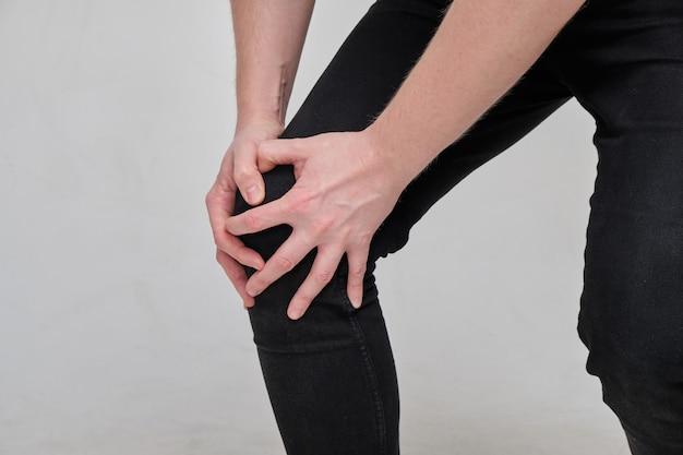 Kulawy mężczyzna w dżinsach masuje mu kolano. koncepcja bólu nóg.